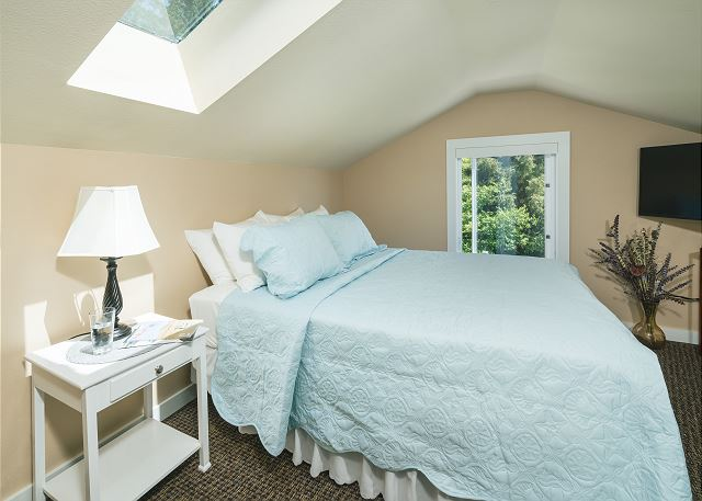 A skylight and large window make this room feel like you are asleep in the trees