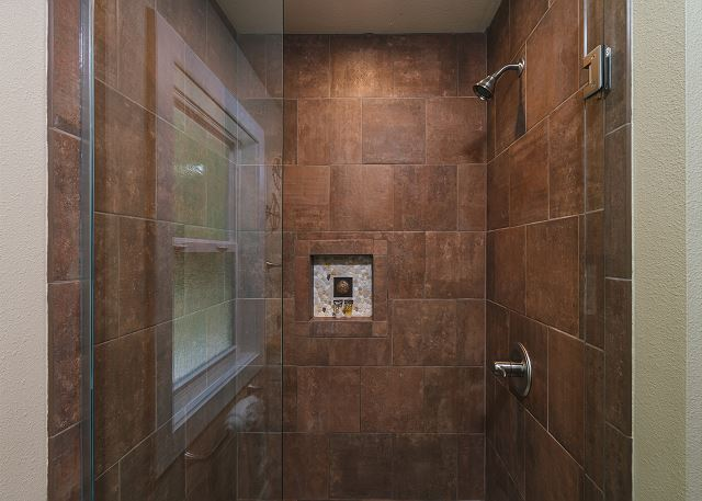 Walk-in shower in the master bath has thoughtful tile accents