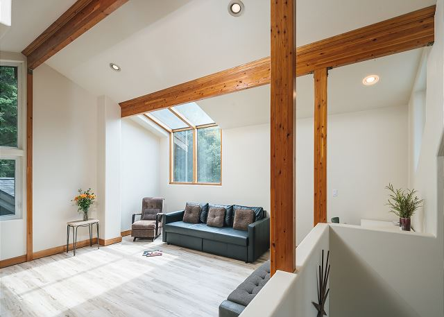 The loft perched above the two story living room has a sofa bed and additional seating