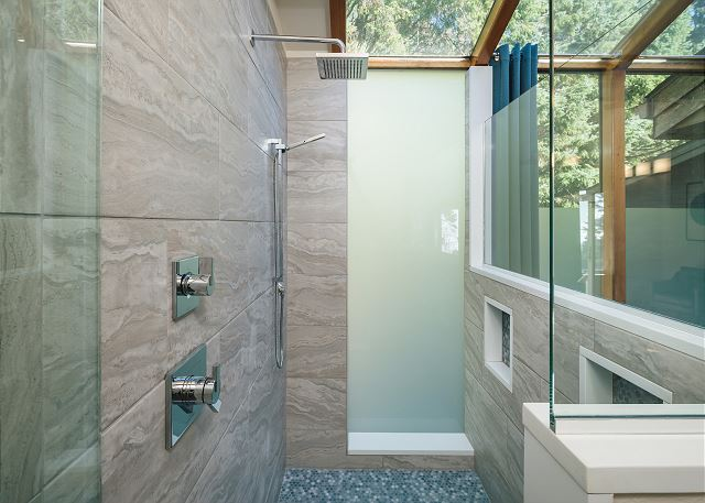 Double shower heads and overhead glass ceiling give the feeling of a peaceful outdoor shower