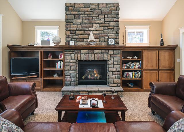 Cozy and dramatic all at once, this living room has vaulted ceilings and a gas fireplace reaching from floor to sky