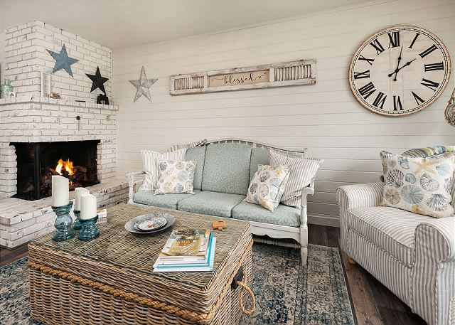 This beautiful beachy living room has a corner gas fireplace