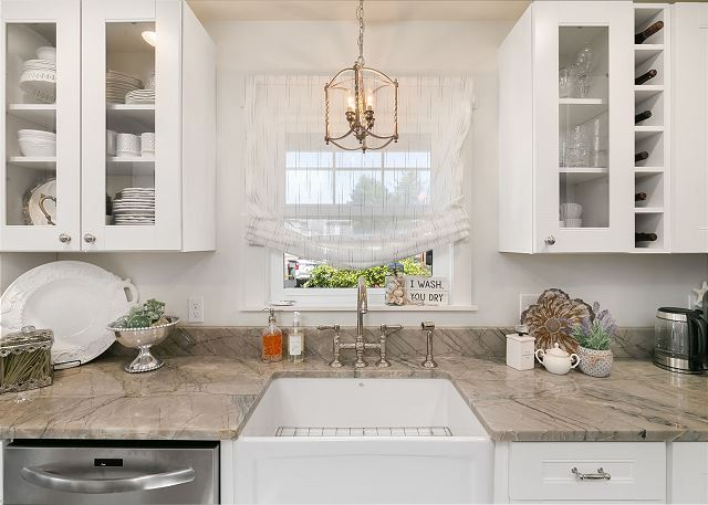 Thoughtful touches like a built in wine rack and glass door cabinetry make this kitchen feel extra special