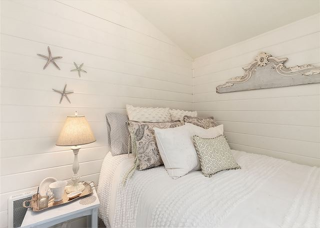 This bedroom with shiplap walls and vaulted ceilings makes excellent use of a cozy space