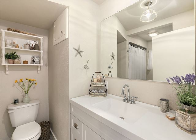 The bathroom has a large vanity and shower/tub combo