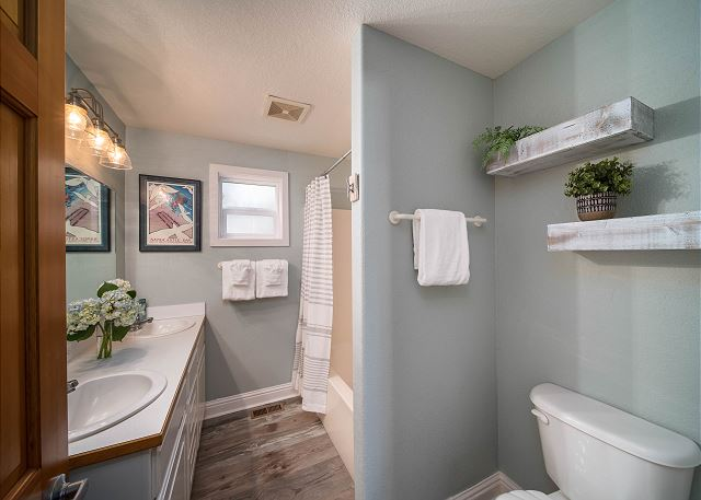 Full bathroom with tub/shower enclosure across the hall from the queen bedroom.