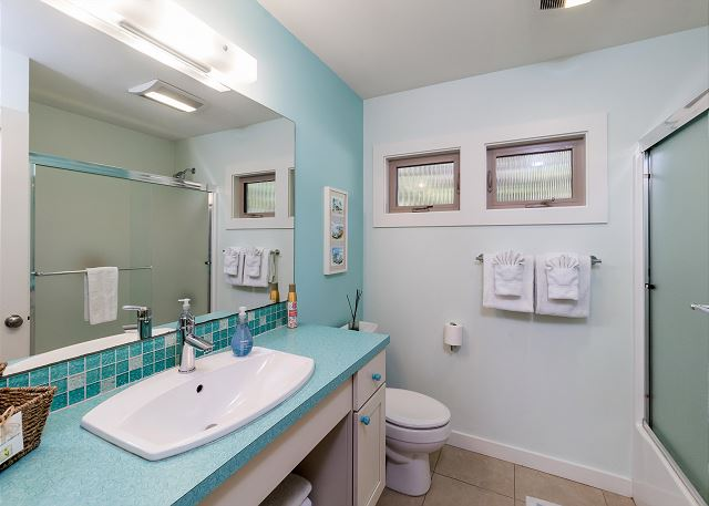 2nd bathroom with tub/shower -all done up in fun surf decor and sea green colors