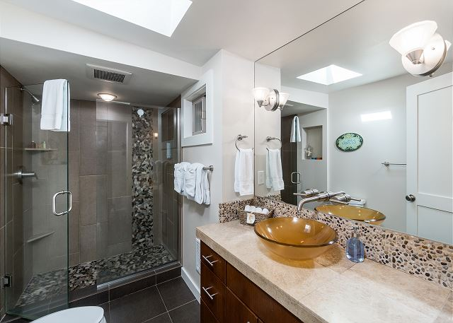 Indulge in the main bathroom with pebble tiled shower, skylight, and vessel sink