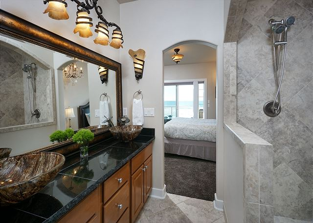 Luxurious en-suite master bath includes walk-in pebble floored shower and double sinks