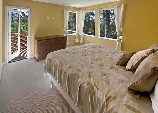 Master suite with king bed, private balcony, en suite bathroom, and large walk-in closet