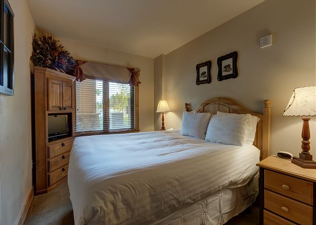 The bedroom features a queen-sized bed with Ivory White Bedding and a flat screen TV.