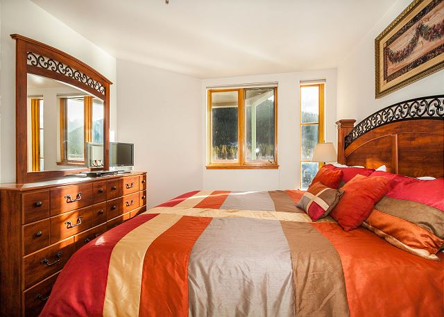 The bedroom features a king-sized bed, a flat screen TV and beautiful lake and mountain views.