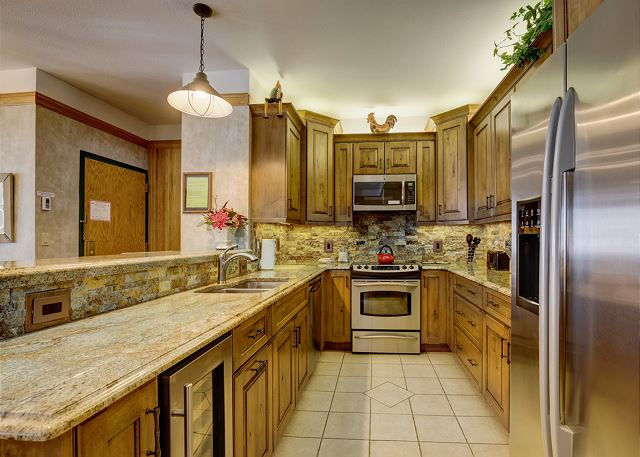 The kitchen features stainless steel appliances and granite countertops.