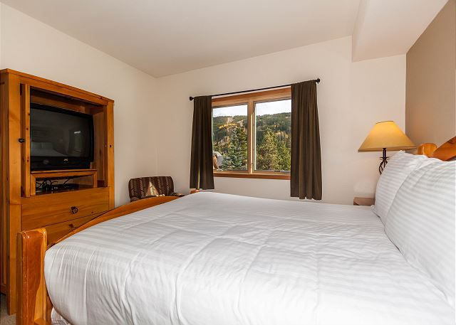 The second master bedroom features a queen-sized bed with Ivory White Bedding and a television.
