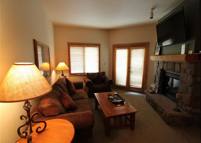 Living room features a sleeper sofa, gas fireplace and flat screen TV.