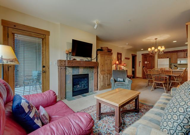 The living area features a flat screen TV mounted above a beautiful gas fireplace.