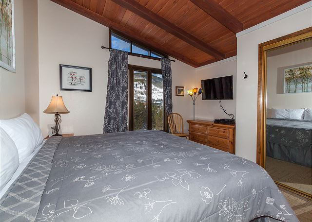 The bedroom features a king-sized bed and a flat screen TV.