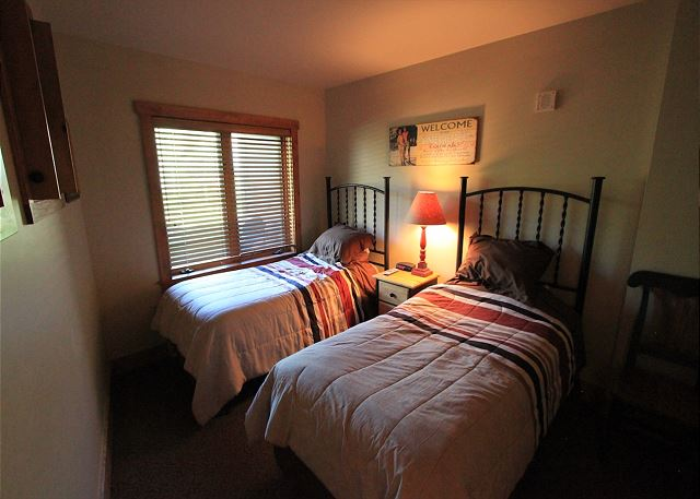 Guest bedroom features two twin-sized beds and a flat screen TV.