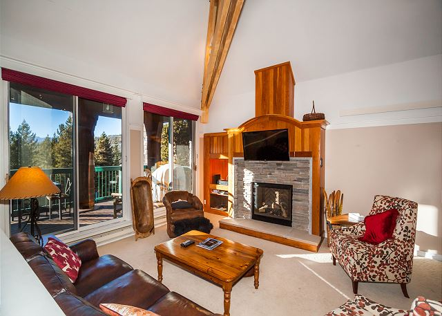 The living area features a flat screen TV mounted above gas fireplace and scenic views.