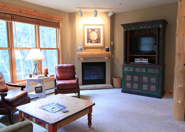 Living room features a gas fireplace, flat screen TV and beautiful views.