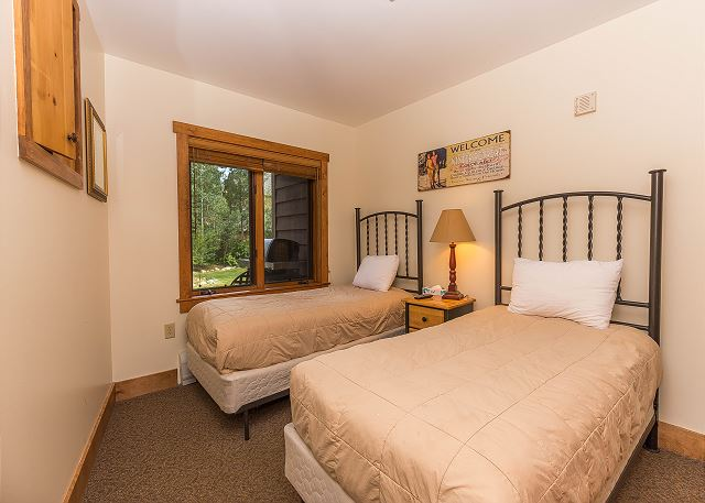 The guest bedroom features two twin-sized beds and flat screen TV.