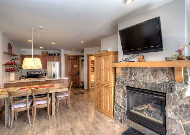 The living room features a flat screen TV mounted above a beautiful gas fireplace and a sleeper sofa.