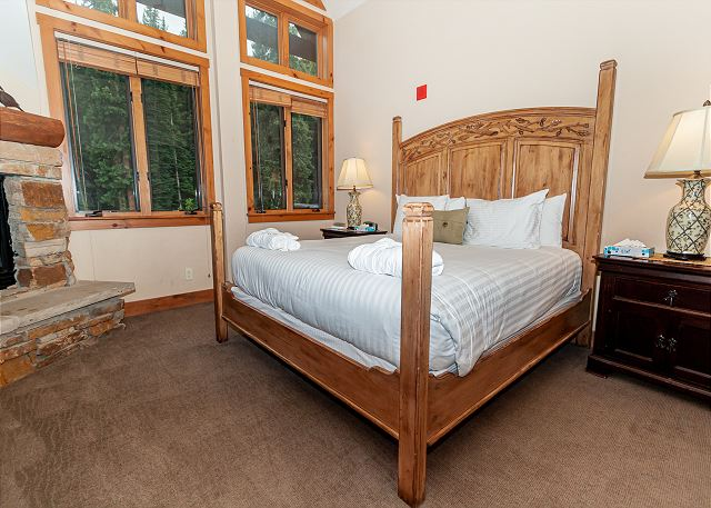 The first master bedroom features a king-sized bed, a gas fireplace and a flat screen TV.