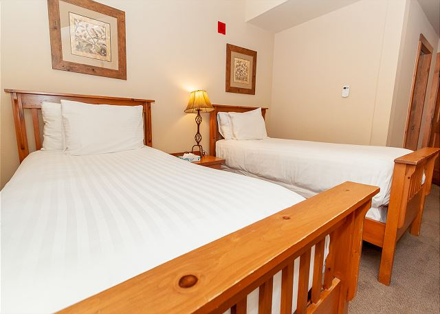 The first guest bedroom features two extra-long twin-sized beds, a flat screen  TV and an en suite bathroom.