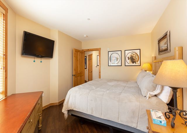 The second master bedroom features a queen-sized bed and a flat screen TV.