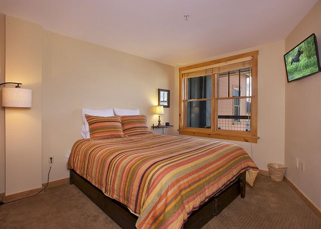 Guest bedroom features a queen-sized bed and a mounted flat screen TV.