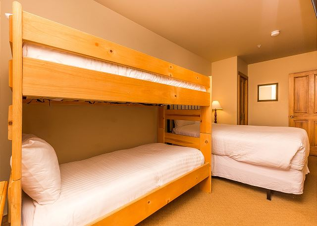 The guest bedroom features a queen-sized bunk bed and a twin-sized bunk bed with Ivory White Bedding. There is a mounted flat screen TV as well.
