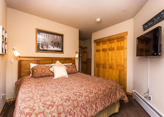 The master bedroom features a king-sized bed, a mounted flat screen TV and access to the deck.