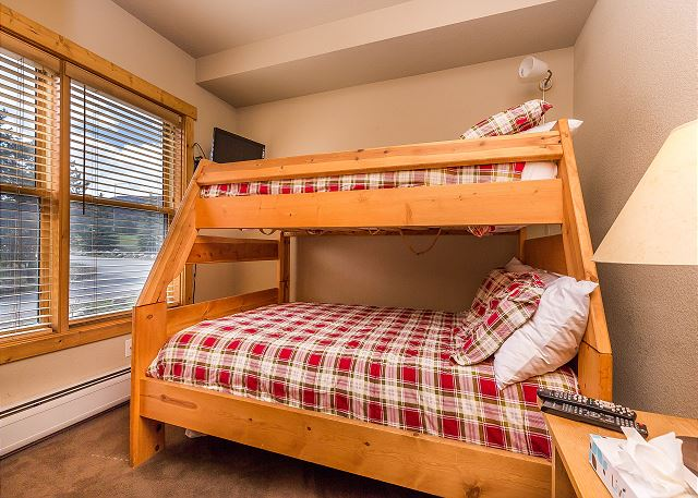 The guest bedroom features a twin-over-full bunk bed and a mounted flat screen TV.
