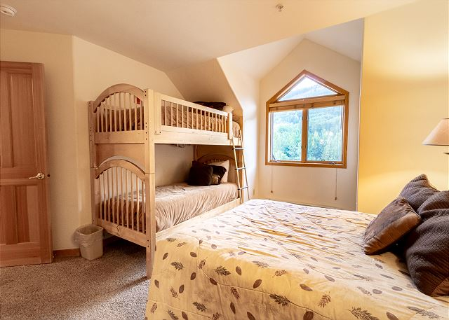 The third guest bedroom features a queen-sized bed and a bunk bed.