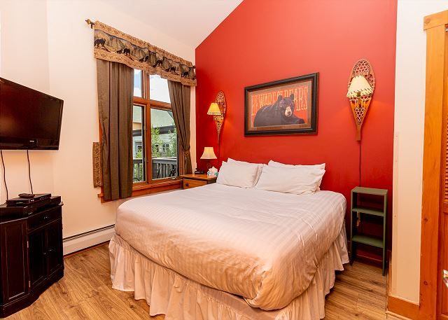 The master bedroom features a king-sized bed with our Ivory White bedding and a mounted flat screen TV.