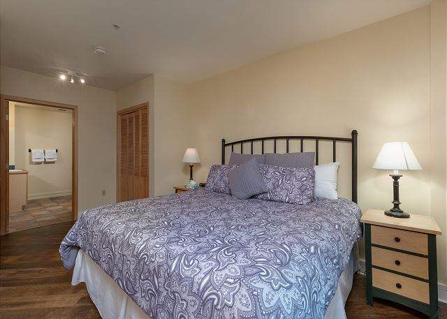 The master bedroom features a king-sized bed, a mounted flat screen TV and an en suite bathroom.