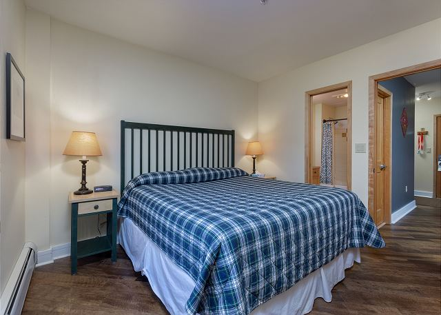 The guest bedroom features a king-sized bed, a mounted flat screen TV and its own entrance to the guest bathroom.