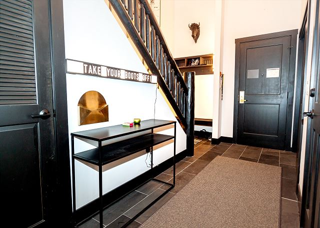 View of entryway. Private laundry is located through the door beneath the stairs.