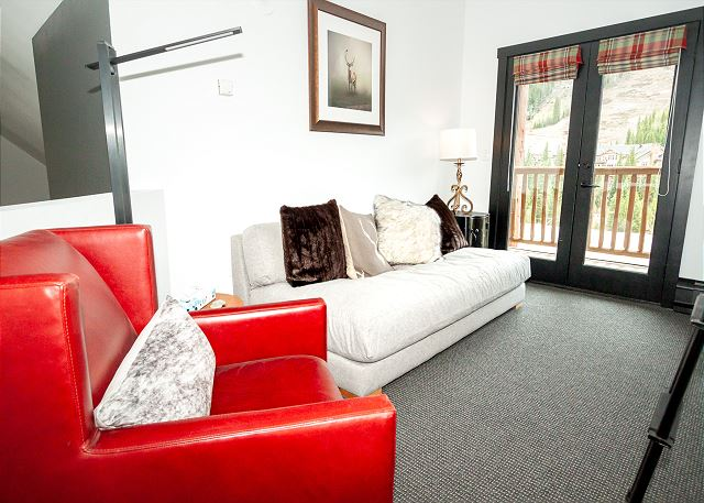 The upstairs loft features a bunk bed, a sofa, and chair. It has its own private balcony with beautiful ski slope views.