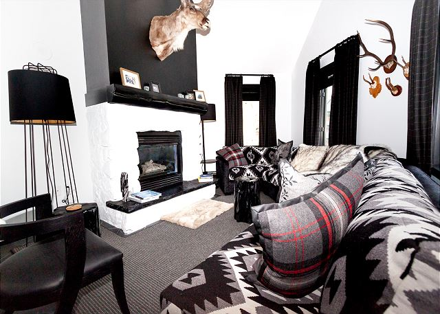 The second living area features a comfortable sectional sofa and its own fireplace.