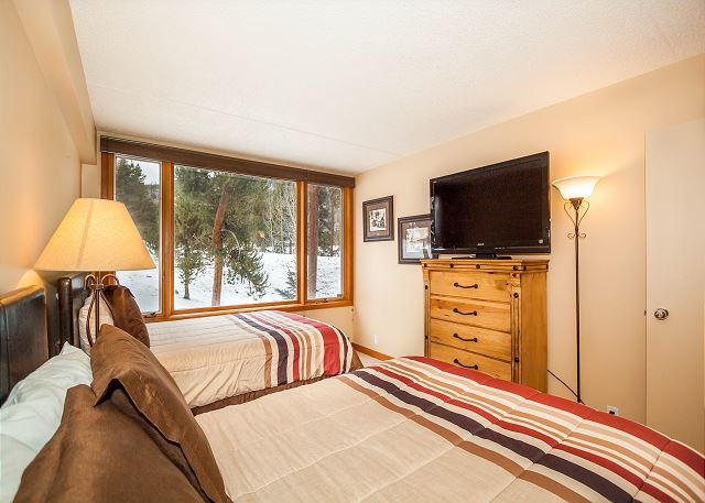 The guest bedroom features two full-sized beds, a flat screen TV and beautiful views.