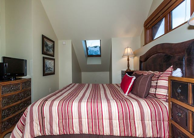 The third master bedroom features a queen-sized bed and a flat screen TV.