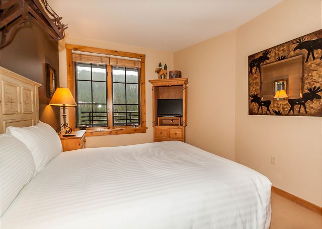 The bedroom features a queen-sized bed with Ivory White Bedding, a flat screen TV and beautiful ski slope views.