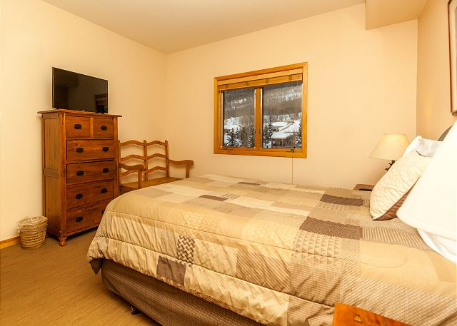 The first guest bedroom is downstairs and has a queen-sized bed and a flat screen TV.