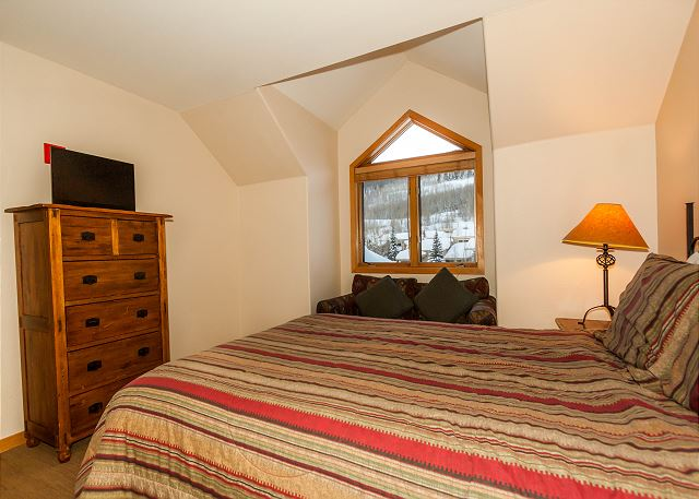 The second guest bedroom is upstairs and has a queen-sized bed, a flat screen TV, and its own private bathroom.