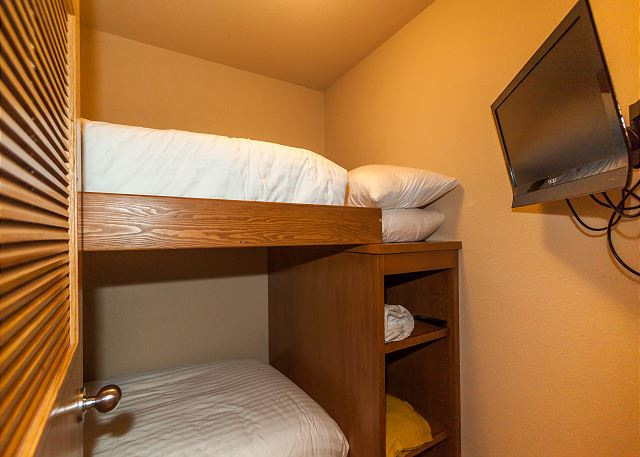The guest sleeping quarters are in a small room and feature a twin-sized bunk bed with Ivory White Bedding and a mounted flat screen TV.