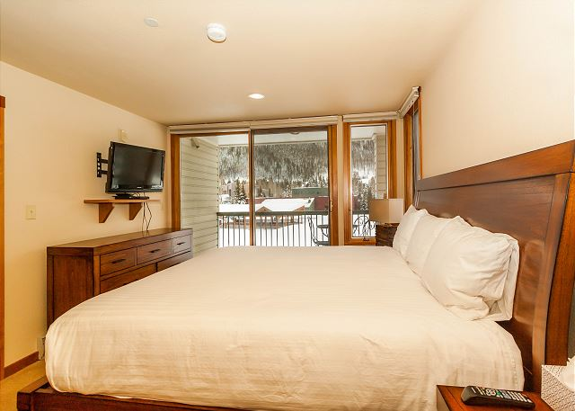 The master bedroom features a king-sized bed with Ivory White Bedding, a flat screen TV and its own private balcony with stunning views of Keystone Lake.
