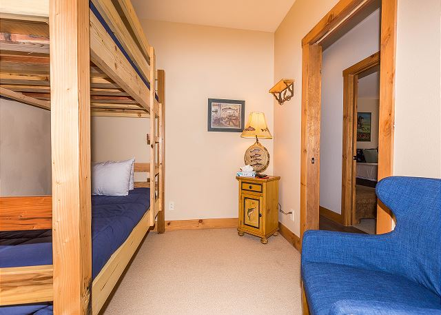 The den serves as the third guest bedroom and has a twin-sized bunk bed and a mounted flat screen TV.