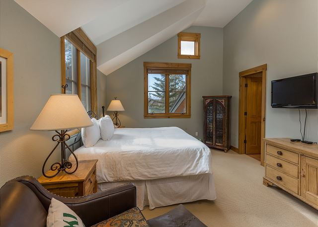 The master bedroom features a king-sized bed, a mounted flat screen TV and a seating area.
