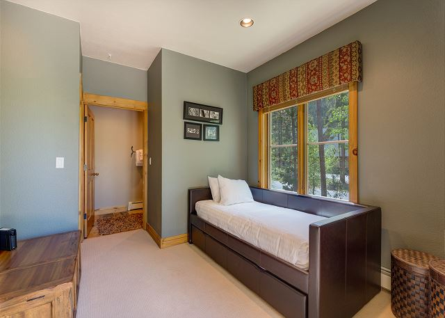 The third guest bedroom is on the main level and features a twin-sized bed with a twin trundle. It has access to the main floor guest bathroom and to the spacious private patio.